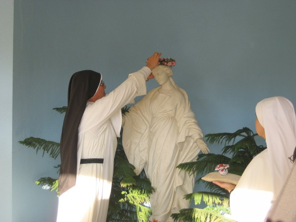 nuns decorating statue of our lady